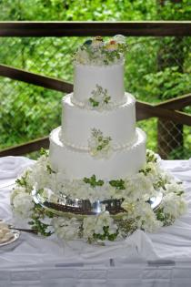 This 3-tiered white wedding cake is both classic and beautiful. The little love birds cake topper is just too cute when mixed with flowers and green berries.