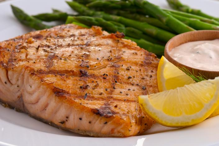 [Image: Our freshly prepared fish is paired with fresh lemon wedges to add a special touch and asparagus.]