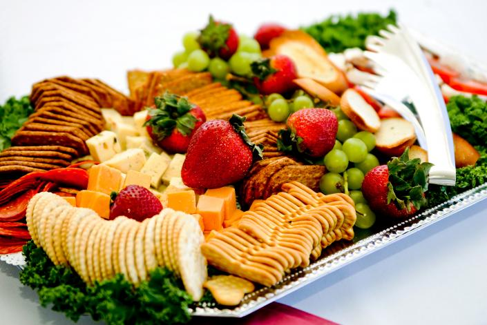 [Image: Cheese and cracker platter paired with fresh strawberries and grapes.]